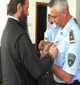The police put handcuffs on Archbishop Jovan in front of the cameras